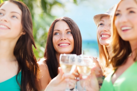 girl drinking: summer holidays, vacation and celebration - girls with champagne glasses