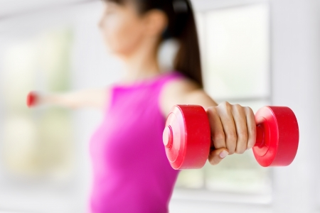 home trainer: sport and recreation concept - sporty woman hands with light red dumbbells