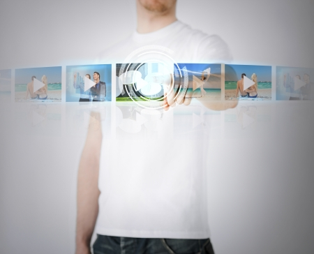 technology, internet, tv and virtual screens concept - man pressing button on virtual screen with videos photo