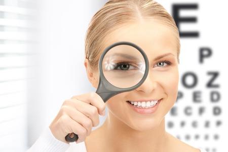 examen de la vista: la medicina y el concepto de la visi�n - mujer con lupa y gr�fico de los ojos Foto de archivo