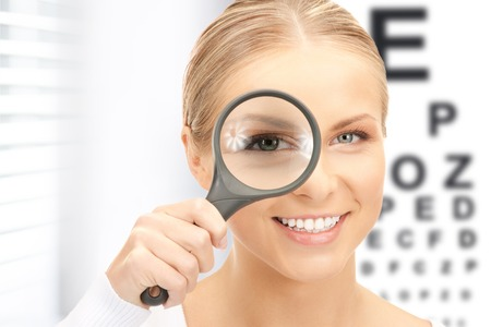 laser surgery: medicine and vision concept - woman with magnifier and eye chart