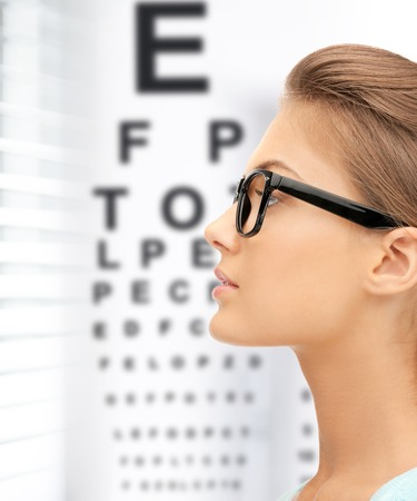 exams: medicine and vision concept - woman in eyeglasses with eye chart Stock Photo