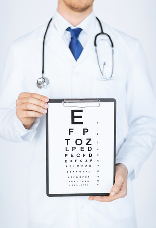 correction: healthcare, medicine and vision concept - male ophthalmologist with eye chart