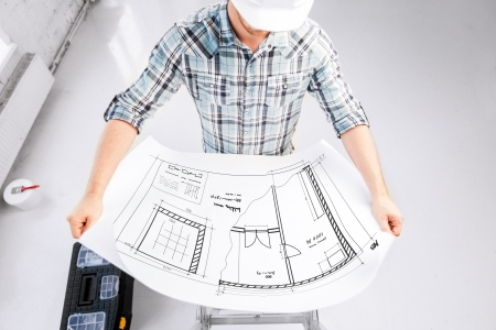 building plans: architecture and renovation concept - male architect in helmet with blueprint Stock Photo
