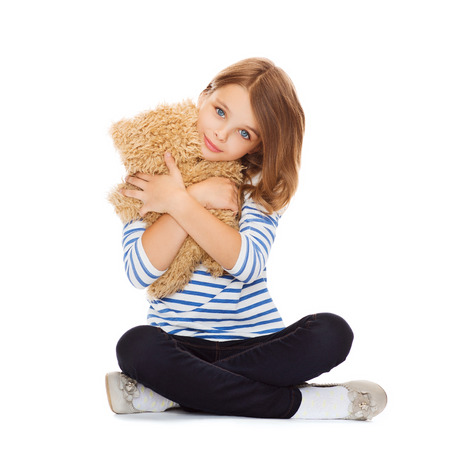 childhood, toys and shopping concept - cute little girl hugging teddy bear Фото со стока