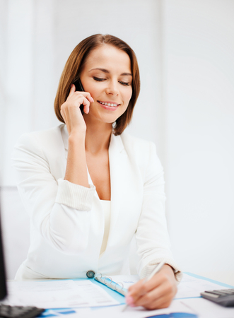business concept - smiling businesswoman with smartphone in office photo
