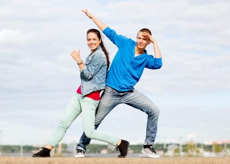 teenage couple: summer holidays, teenage and dancing concept - couple of teenagers dancing outside