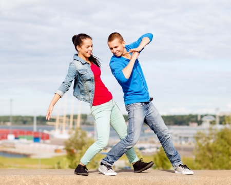 salsa dance: summer holidays, teenage and dancing concept - couple of teenagers dancing outside