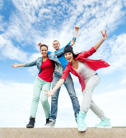 smiling teenagers: sport, dancing and urban culture concept - group of teenagers dancing
