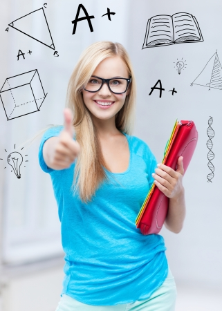 education and school concept - smiling student with folders showing thumbs up photo