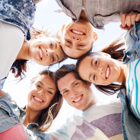 urban youth: summer holidays and teenage concept - group of teenagers looking down Stock Photo