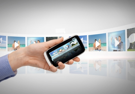 digi: technology, internet, tv and news concept - woman hand with smartphone, videos and virtual screen Stock Photo