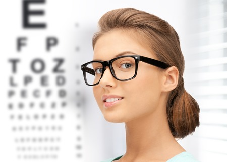 medicine and vision concept - woman in eyeglasses with eye chart photo