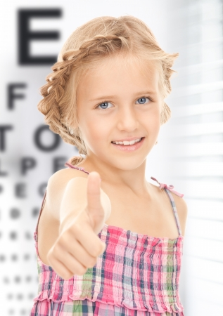 medicine and vision concept - girl with optical eye chart photo