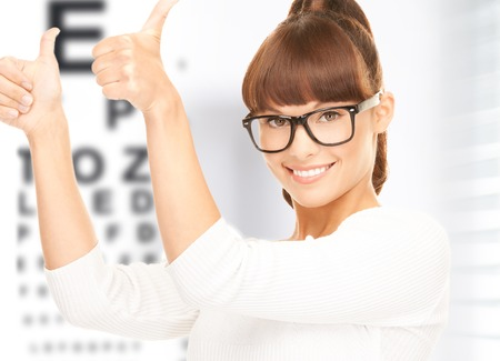 correcting: medicine and vision concept - woman in eyeglasses with eye chart Stock Photo