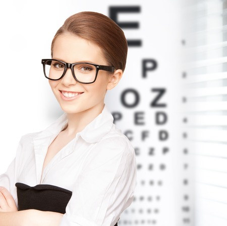 testing vision: medicine and vision concept - woman in eyeglasses with eye chart Stock Photo
