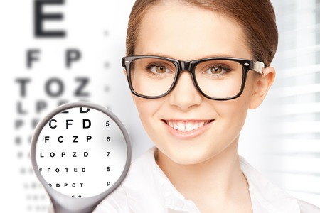 exams: medicine and vision concept - woman with magnifier and eye chart