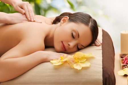 spa therapy: beauty, holidays and spa concept - woman in spa salon getting massage