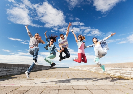 leaping: summer, sport, dancing and teenage lifestyle concept - group of teenagers jumping Stock Photo