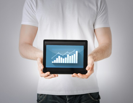 business and finance - man hands holding tablet pc with graph photo