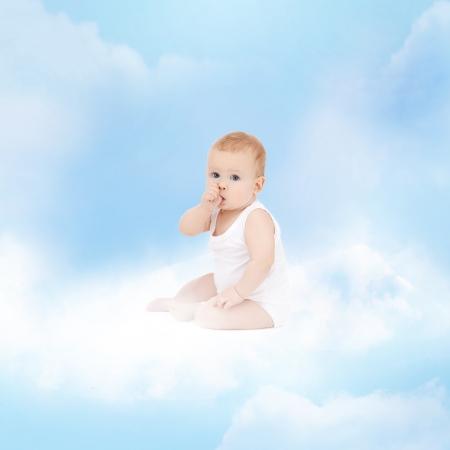 baby angel: infanzia e figlio concetto di cura - sorridente bambino seduto sulla nuvola