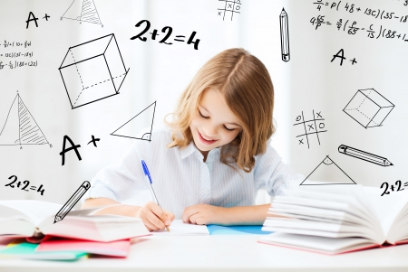 making notes: education and school concept - little student girl studying at school
