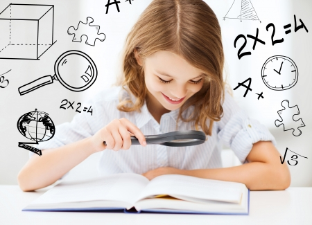 education and school concept - little student girl reading book with magnifier at school photo