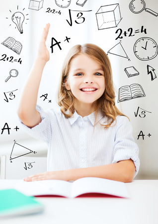 scholar: education and school concept - little student girl studying and raising hand at school Stock Photo