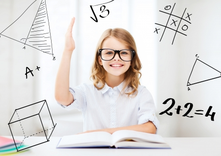 education and school concept - little student girl studying and raising hand at school photo