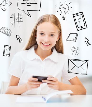niños platicando: la educación, la escuela, la tecnología y el concepto de Internet - niña estudiante con el teléfono inteligente en la escuela