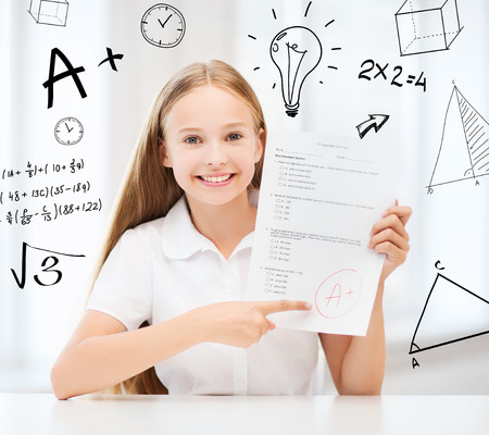 grading: education and school concept - little student girl with test and A grade at school