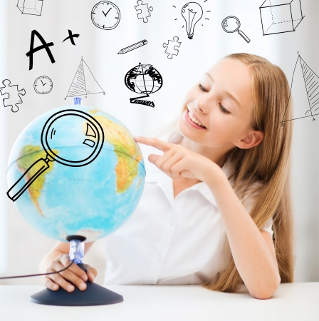 schoolkid search: education and school concept - little student girl with globe at school