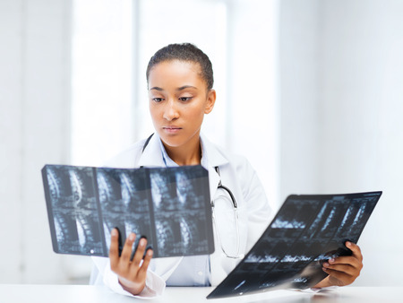 radiology: healthcare, medical and radiology concept - african doctor looking at x-rays