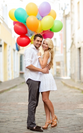 helium: summer holidays, celebration and dating concept - couple with colorful balloons in the city Stock Photo