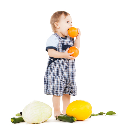 nice food: childhood and healthy food concept - cute toddler with vegetables eating orange