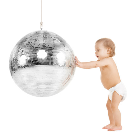 childhood and toys concept - cute little toddler playing with disco ball photo