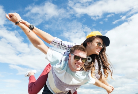summer holidays and teenage concept - teenagers having fun outside photo