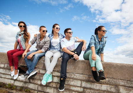 chilling out: summer holidays and teenage concept - group of teenagers hanging out outside