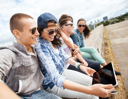 summer holidays, teenage and technology concept - group of teenagers looking at tablet pc