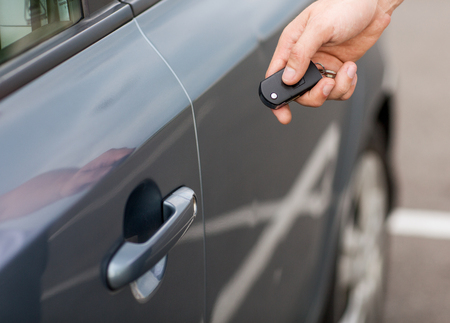 transportation and ownership concept - man with car key outside photo