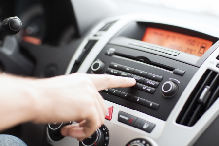 audio: transportation and vehicle concept - man using car audio stereo system Stock Photo