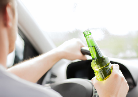 drunk driving: transportation and vehicle concept - man drinking alcohol while driving the car
