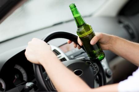 alcoholismo: transporte y veh�culo de concepto - hombre bebiendo alcohol mientras se conduce el autom�vil Foto de archivo