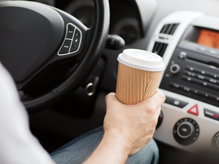 carelessness: transportation and vehicle concept - man drinking coffee while driving the car