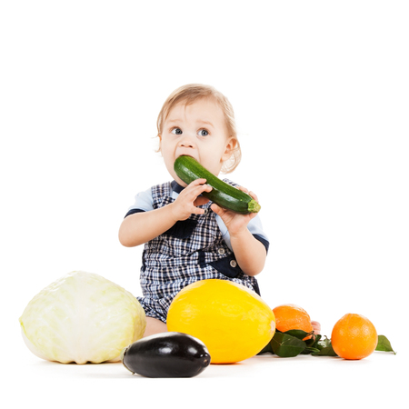 childhood and healthy food concept - cute toddler with vegetables and fruits eating squash photo