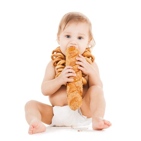 childhood and food concept - cute todler eating long bread photo