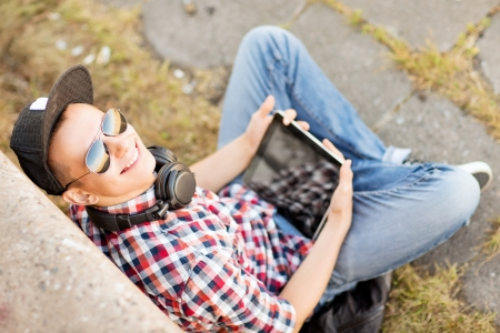 summer holidays, teenage and technology concept - teenager with headphones and tablet pc outside photo