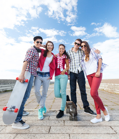 summer holidays and teenage concept - group of teenagers with skates outside photo