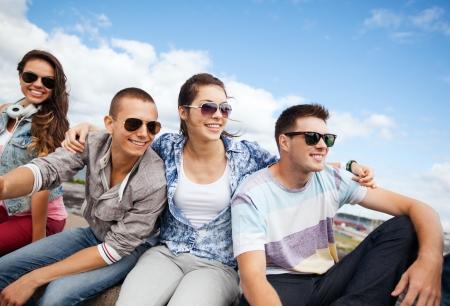 sunglasses: vacaciones de verano y el concepto de adolescente - grupo de adolescentes colgando fuera