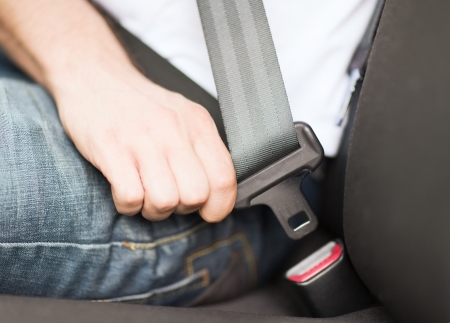 transportation and vehicle concept - man fastening seat belt in car photo